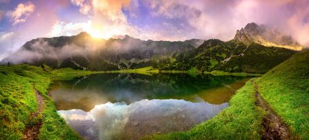 Magnificent sunrise at a lake in the Alps with mountains, colorful clouds and wafts of mist reflected in the clear water and paths leading through the vibrant green grass