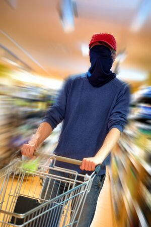 Shopping man being so afraid of the coronavirus that he covers his whole face with a scarf as a protective mask in a supermarket. A concept shot with radial blur effect