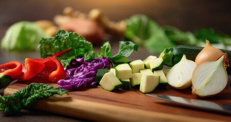 Cooking vegetables on a wooden cutting board. A closeup with shallow focus showing colorful, nutritious and delicious food ingredients as a healthy lifestyle concept.