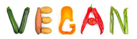 The lettering vegan arranged with different colorful vegetables on white: zucchini, potatoes, butternut squash, red peppers and asparagus. Concept studio shot Reklamní fotografie