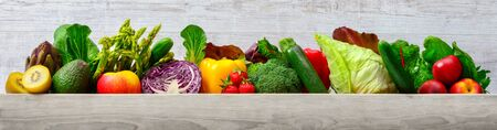 Arrangement of fruits and vegetables in many appetizing colors in a row on wooden light gray background, concept for a healthy plant-based lifestyle and fitness, with copy space