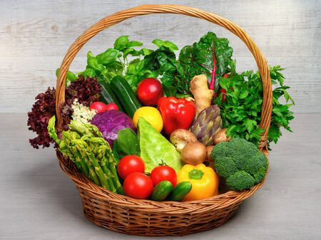 Vintage basket filled with an arrangement of mixed colorful vegetables on light background, looking fresh, healthy and appetizing, a whole food nutrition concept