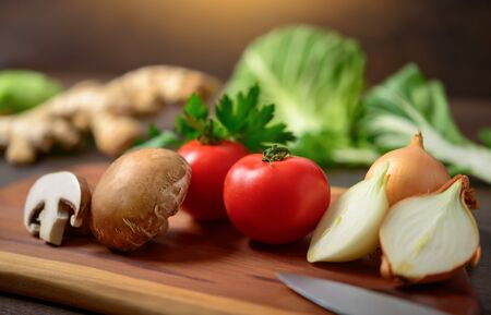 Preparing vegetables on a wooden cutting board to cook. A closeup with shallow focus showing colorful, nutritious and delicious food ingredients as a healthy lifestyle concept. Reklamní fotografie