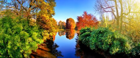 Colorful flora around a blue lake in a park in autumn, with red, green and yellow foliage, nice weather and sunshine, a panoramic landscape shot
