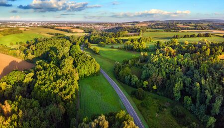 Idyllic German landscape shot from above in early morning sunlight: meadows and forests with blue sky and a road leading to a small town on the horizon