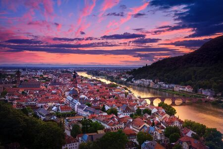 Romantic aerial view of Heidelberg with Neckar river, Germany, a dramatic afterglow with vibrant red and purple colors after sunset