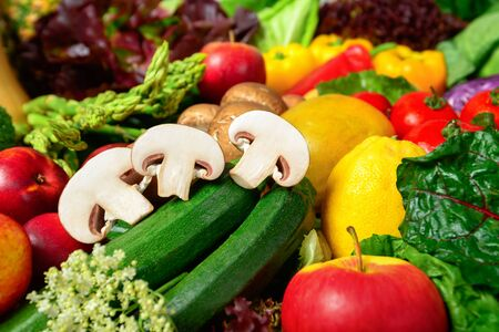 Colorful appetizing fruits and vegetables, a delicious looking closeup studio shot motivating for self-care and leading a healthy lifestyle, with cut mushrooms in focus