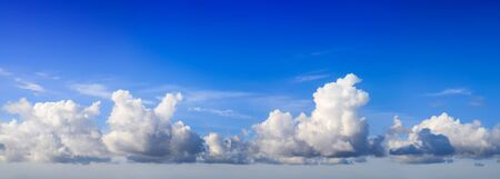 White fluffy yet majestic cumulus clouds on deep blue sky background, panoramic format Reklamní fotografie