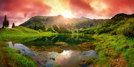 Dramatic sunrise at a lake in the Alps with mountains, red clouds reflected in the clear water and paths leading through the vibrant green grass