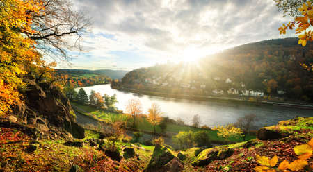 View onto the Neckar river and idyllic landscape near Heidelberg, Germany, as the sun is about to set behind a hill on a colorful autumn day