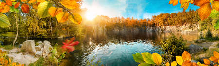 Magnificent autumn landscape panorama with colorful foliage framing a beautiful blue lake, with sun and blue sky Reklamní fotografie