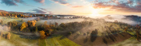 Stunning aerial panorama of a misty rural landscape at sunrise, with colorful autumn trees, fields and meadows, blue sky, trees casting shadows and beautiful wafts of mist