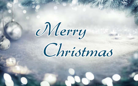 Christmas card with snow background and Merry Christmas lettering framed by fir branches, lights and ornaments