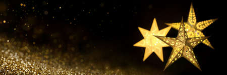 Ornate gold star lanterns for Christmas on black background with golden stardust, extra wide format with copy space