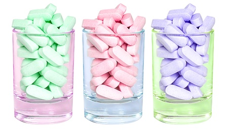 Three small colourful glasses filled with bright pills.