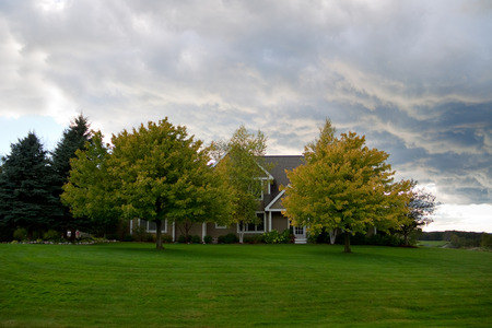 American suburban house behind the trees in autumn stormy day Stock Photo