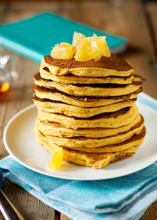 Stack of pumpkin pancakes with oranges Stock Photo
