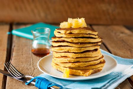 Pile of pumpkin pancakes on white plate