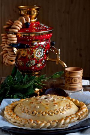 Traditional Russian pie Kournik and Samovar