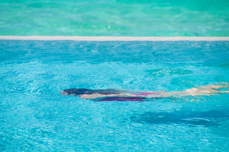 Girl in red swimming suit swimming underwater in a blue pool Reklamní fotografie