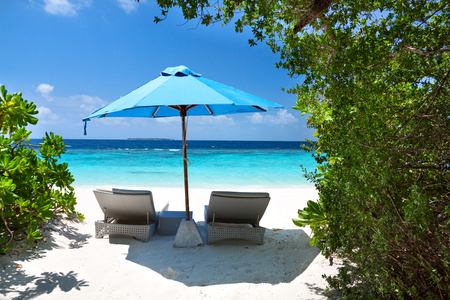 Two lounge chairs with sun umbrella on a beach. Maldives resort