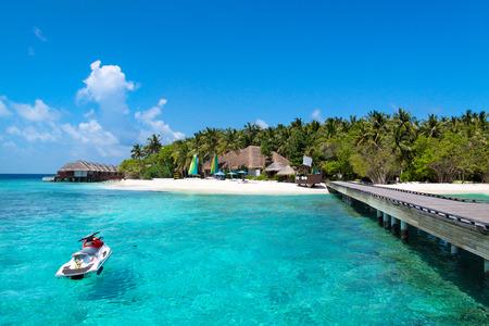 Landscape of Maldives Male Atoll sandbank island. Jet ski at the white sandy beach