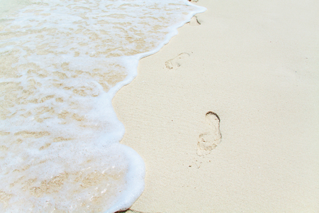ocean water: Footprints on sea shore. Ocean water wave. Beach Vacation