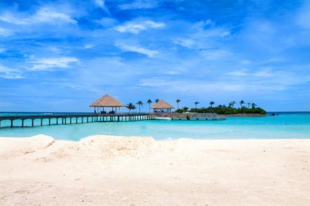 Tropical Maldives island resort jetty under beautiful cloudy sky.