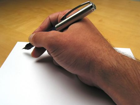 uncomplete: Close-up of hand beginning to write on white paper Stock Photo