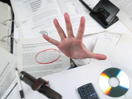 affirmative: Business hand coming out of a pile of work on an office desk expressing need of help! Hand is focused and sharp, background is motion-blurried. Stock Photo