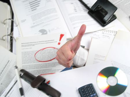 ok symbol: Business hand coming out of a pile of work on an office desk showing an OK symbol. Hand is focused and sharp, background is motion-blurried.