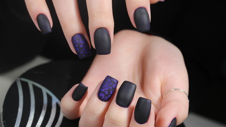 Design of manicure matt black and blue nails Фото со стока