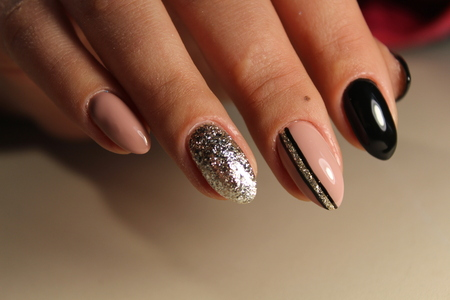 Design of black and beige nails with abstraction
