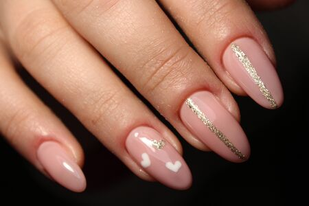 Manicure - Beauty treatment photo of nice manicured woman fingernails. Feminine nail art with nice glitter, pink and white nail polish. Archivio Fotografico
