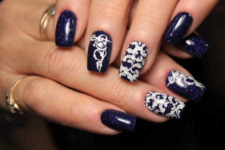 Christmas Nail art manicure. Winter Holiday style bright Manicure with gems Christmas tree and snowflakes. Bottle of Nail Polish.