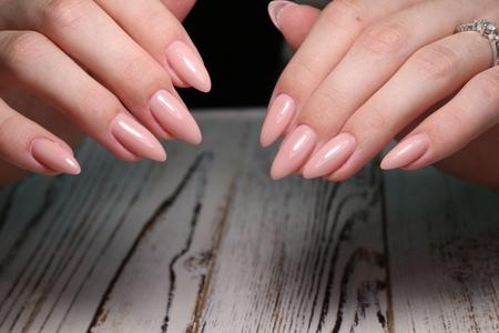 Beautiful groomed womans hands on the light gray background. Reklamní fotografie