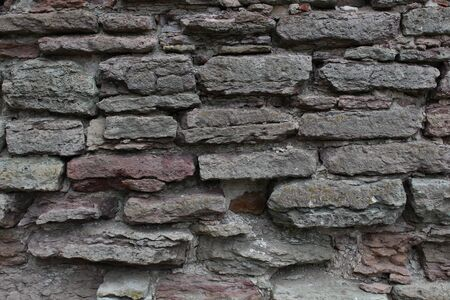 Destroyed by time and precipitation brick wall. The Background of old vintage brick wall