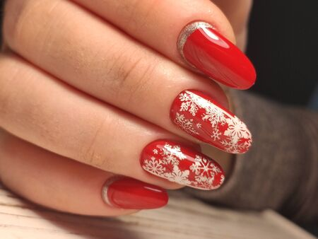 red Christmas manicure with deer and snowflakes and Norwegian pattern with Christmas ball on the tree