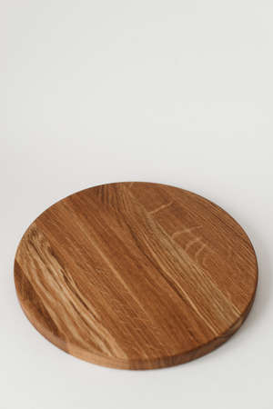 Wooden tray with a round shape. Beautiful ash wood texture. Cookware made of natural materials.