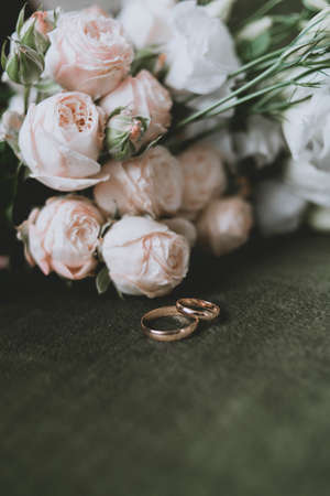 wedding bouquet and rings on a green background. Wedding preparations Archivio Fotografico