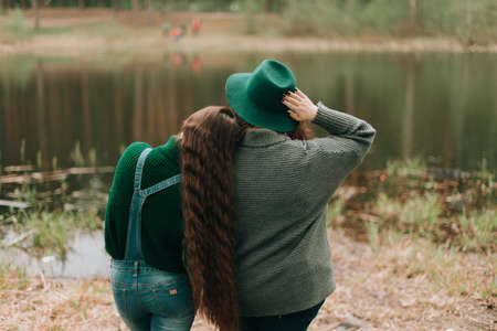 two girlfriends stand by the lake, spring landscape, green color.
