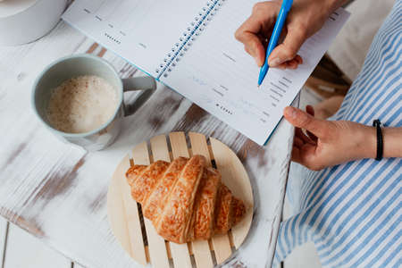 business breakfast puff cake tea and notebook with pen on the table business