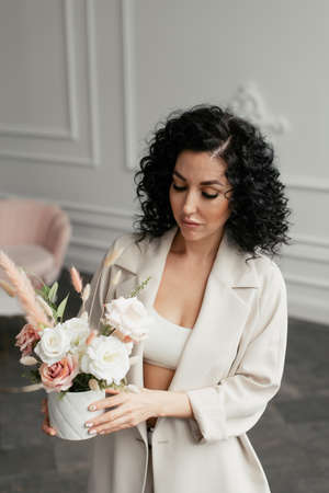 Woman with black curly hair with a bouquet of flowers looked down Stock fotó