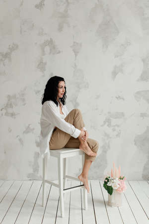 stylish brunette girl with feet in beige pants and a white shirt sits on a high white chair Reklamní fotografie