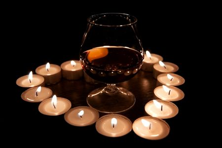 Valentines Day composition with one glass of cognac in the center of candle burn heart photo