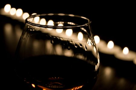 impassioned: one glass of cognac in the candle burn Stock Photo
