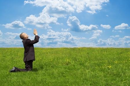 man praying: businessman praying on grass field