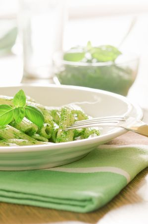 pasta with sauce pesto on table photo