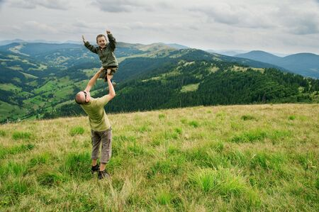 son on father hand in mountain photo