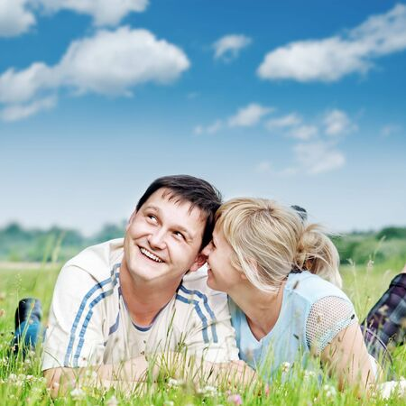 smiling couple lie in field  photo